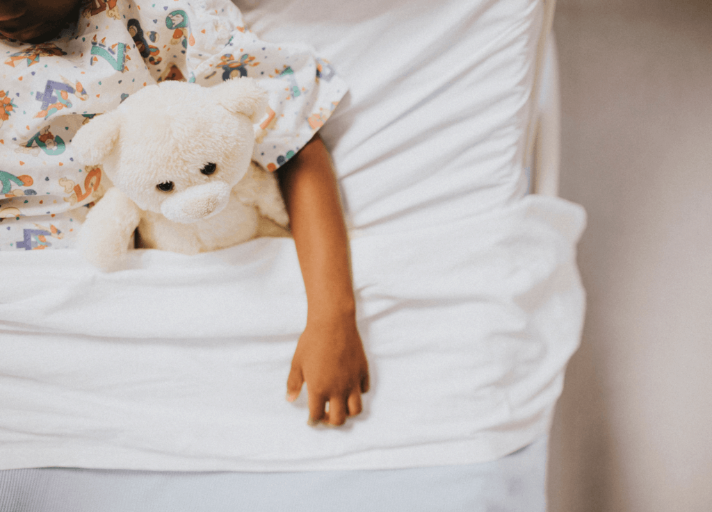 child in hospital bed with teddy bear