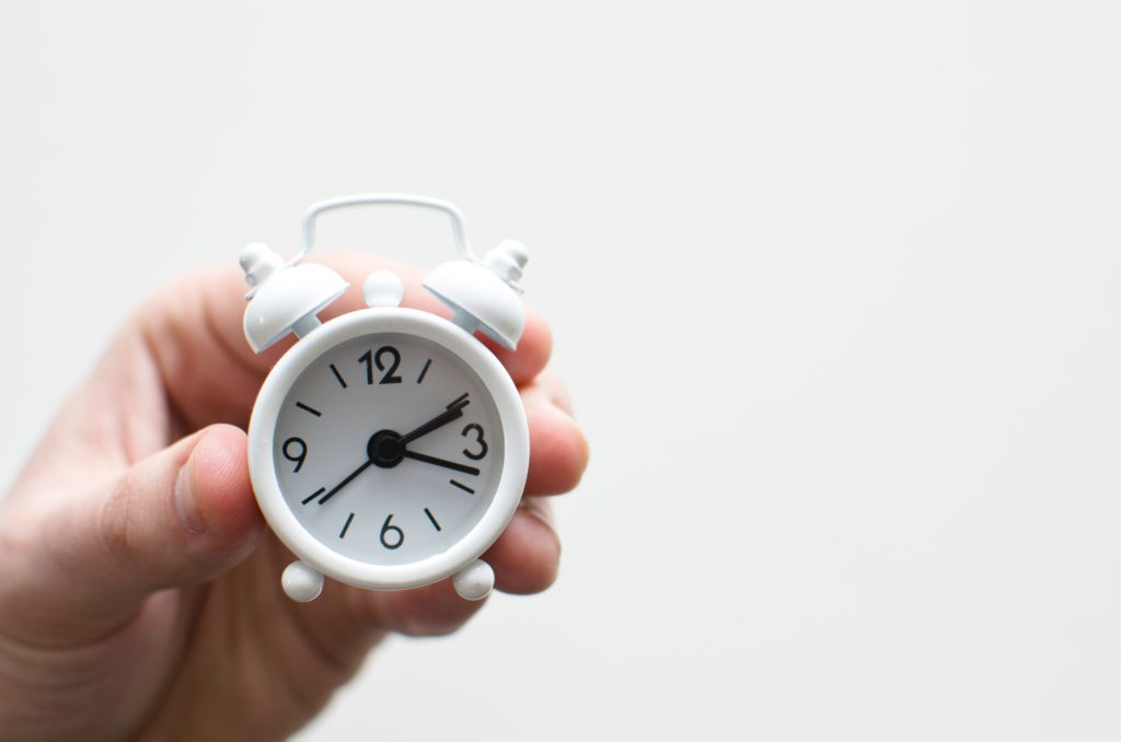 person holds small analog alarm clock