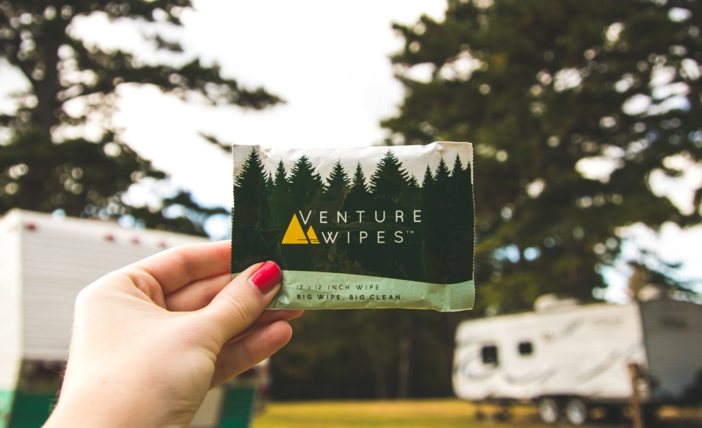 venture wipes held up by female hand with RVs in the back