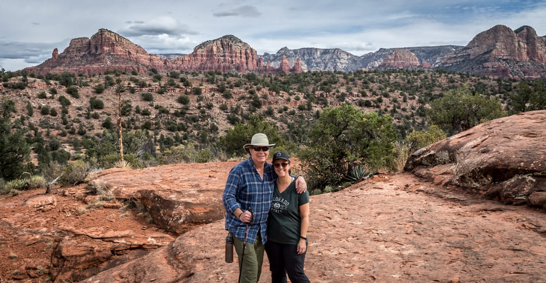 Writer and her husband on a hike, standing in front of Cathedral Rock in Sedona, AZ